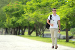 Handsome college student walking by at college park with backpac. Portrait of handsome college student walking by at college park with backpack and holding a Royalty Free Stock Image