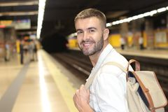 Handsome commuter smiling while waiting for his train.  Royalty Free Stock Photos