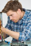 Handsome computer engineer repairing faulty pc Stock Photography