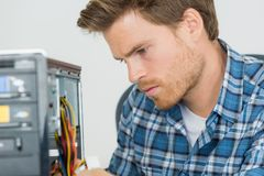 Handsome computer engineer repairing faulty pc Royalty Free Stock Photo