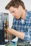 Handsome computer engineer repairing faulty pc Royalty Free Stock Photography