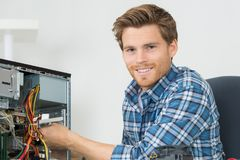 Handsome computer engineer repairing faulty pc Stock Images