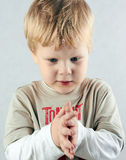 Handsome concentrated boy crosses his arms. royalty free stock photography
