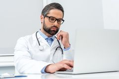 Handsome concentrated doctor using. Laptop Stock Images