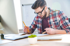 Handsome concentrated man working with blueprint using ruler and pencil Royalty Free Stock Photos