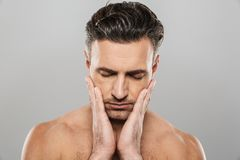 Handsome concentrated mature manwith eyes closed touching his face. Image of handsome concentrated mature man standing isolated over grey wall background naked royalty free stock photo