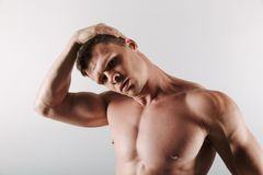 Handsome concentrated young sportsman stretching exercises. Photo of handsome concentrated young sportsman standing isolated over grey background make stretching Stock Photography