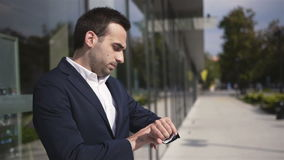 Handsome concerned businessman waiting for someone outdoors the office building. stock footage