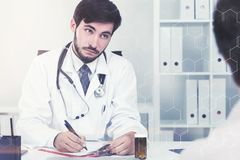 Bearded doctor talking to patient in office, toned Stock Photo