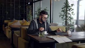 Handsome condfident man sitting in cafe and with a cup of green tea. stock video