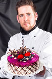 Handsome confectioner with cake Royalty Free Stock Image