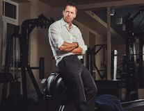 Handsome confident businessman in formal clothes came to the gym for training after a hard day`s work. Stock Image