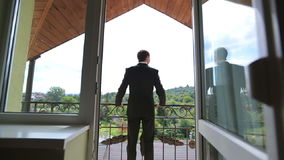 Handsome confident groom in black suit standing on the balcony leaning on railing and looking on the green forest on