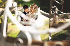 Handsome confident groom hugging white dress blonde bride carria Royalty Free Stock Image