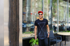 Handsome confident guy arab man holds smart phone, smiles and po Stock Photos