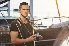 Handsome confident guy with stylish haircut standing near awesome yacht, holding camera, staring seriously and being royalty free stock photography