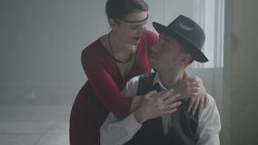 Handsome confident mafia boss in a hat and a vest sitting in an abandoned building. The elegant woman in red dress. Coming from behind and hugging the man stock video