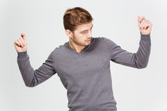 Handsome confident man in grey pullover dancing with raised hands Stock Photos