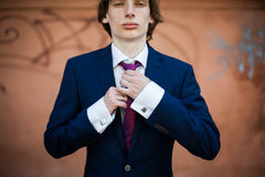 Handsome confident pale groom in dark blue suit posing and touch Stock Images