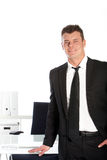 Handsome businessman standing at his desk Royalty Free Stock Photos