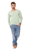 Handsome confident relaxed young man. Handsome confident relaxed handsome young man with a beard posing with his hands in his pockets in jeans and slip slops Stock Photos