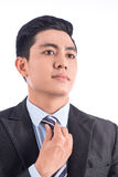 Handsome confident young business man straightening his tie Royalty Free Stock Image