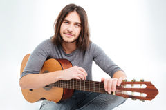 Handsome confident young man with acoustic guitar Stock Photos