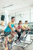 Handsome and confident young man during group class of HIIT indo. Handsome and confident young men smiling while pedaling during group class of HIIT indoor Stock Photos