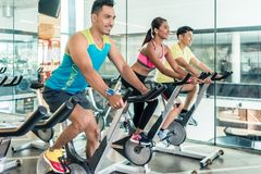 Handsome and confident young man during group class of HIIT indo. Handsome and confident young men smiling while pedaling during group class of HIIT indoor Stock Photography