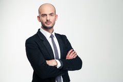 Handsome confisent businessman in black suit standing with folded hands. Handsome confisent young businessman in black suit standing with folded hands over white Stock Photography