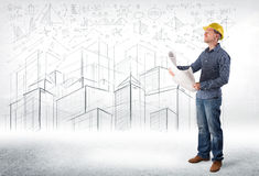 Handsome construction specialist with city drawing in background Royalty Free Stock Photo