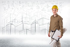 Handsome construction specialist with city drawing in background Royalty Free Stock Photography