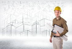 Handsome construction specialist with city drawing in background royalty free stock images