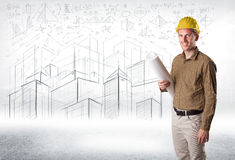 Handsome construction specialist with city drawing in background Royalty Free Stock Image