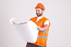 Handsome Construction Worker with Buildingl Plans. Handsome Construction Worker in Safety Helmet and Orange Reflex Jerkin is Holding a Building Plans Isolated on Royalty Free Stock Photos