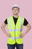 Handsome construction worker with hands on hips over pink background Royalty Free Stock Photography