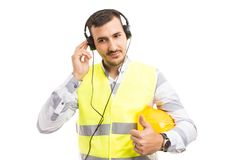 Handsome construction worker listening music on headphones royalty free stock image