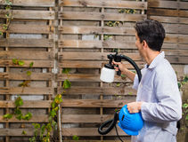 Handsome construction worker using the painting spray gun in outdoors in a wooden wall structure Royalty Free Stock Image