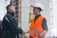 Construction workers in protective helmets and vests are shaking hands while working in the office center royalty free stock images
