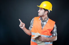 Handsome constructor wearing equipment pointing up royalty free stock photography