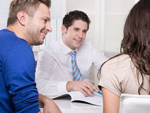 Handsome consultant in shirt and tie with a couple at office. Royalty Free Stock Photo
