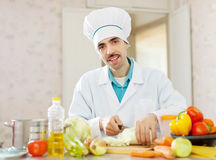 Handsome  cook cooking in kitchen Stock Photos