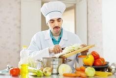 Handsome  cook does vegetarian lunch Stock Photos