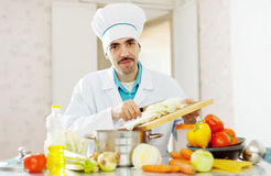 Handsome  cook does veggie lunch Stock Photos