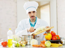 Handsome  cook does veggie lunch Stock Image