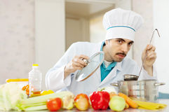 Handsome cook tasting soup Royalty Free Stock Image