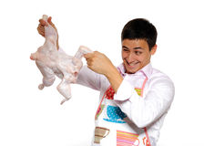 Handsome cooking young man holding chicken Stock Images