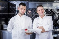 Handsome cooks holding a plate with a dish royalty free stock photography