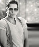 Cool dude. Handsome cool young male model wearing white T-shirt and suspenders with sunglasses Royalty Free Stock Images