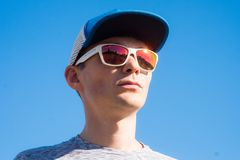Handsome cool young man with sunglasses. And cap royalty free stock photos